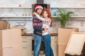 Fotografie happy young couple hugging and smiling at camera while standing between cardboard boxes in new apartment at christmastime