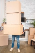 Photo man holding stack of cardboard boxes while moving home