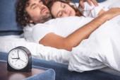 Detailní pohled na budík a mladý pár spolu spíme za