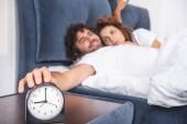 zblízka pohled na budík a mladý pár spolu probuzení