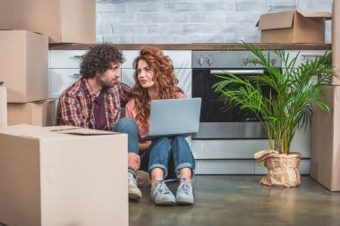 boyfriend and girlfriend sitting with laptop near cardboard boxes on floor in new kitchen and looking at each other