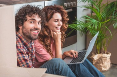 smiling couple sitting on floor with laptop near cardboard boxes in new kitchen