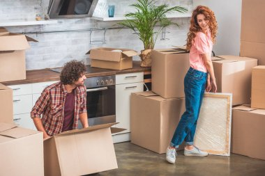 couple unpacking cardboard boxes at new home and looking at each other
