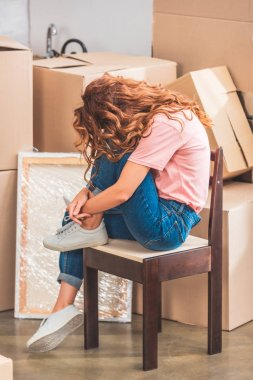 woman with curly red hair sitting on chair near cardboard boxes at new home