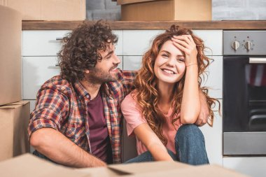 smiling couple sitting on floor near cardboard boxes in new kitchen