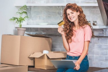 beautiful happy young woman holding credit card and smiling at camera while using laptop in new apartment