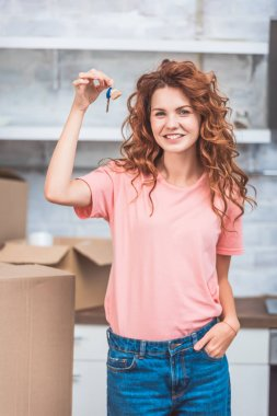 beautiful happy young woman holding key from new apartment and smiling at camera