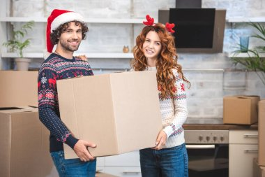 happy young couple holding cardboard box and smiling at camera while relocating in new apartment at christmastime