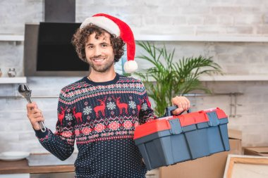 happy young man in santa hat holding toolbox and smiling at camera in new apartment