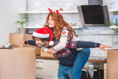 Happy young couple having fun and smiling at camera while moving home at christmastime stock vector