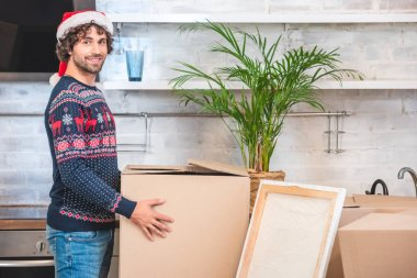 handsome happy young man in santa hat holding cardboard box and smiling at camera during relocation