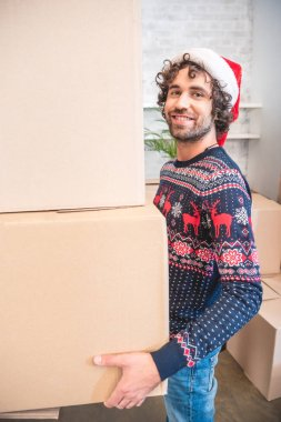 happy young man in santa hat holding cardboard boxes and smiling at camera