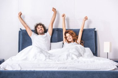 happy young couple stretching arms and waking up together in bedroom