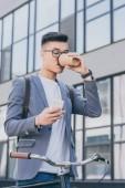 Asiat popíjel kávu jít a při pohledu na smartphone poblíž kolo ve městě