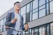 Stylový jistý asijské muž, který držel jedno šálek kávy a smartphone poblíž kolo ve městě