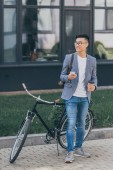 Photo smiling asian man with coffee to go using smartphone and standing near bike