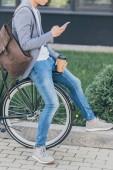 Fotografie Ausgeschnittene Ansicht eines Mannes mit Coffee to go mit Smartphone und Fahrrad