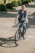 usmívající se asijské muž na kole na kole ve městě