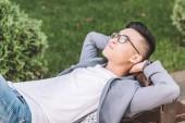 szép stílusos ázsiai ember álmodik, és feküdt a padon