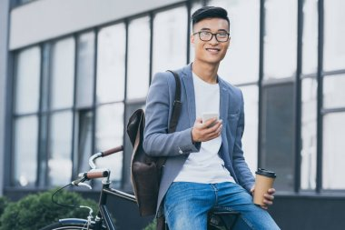 Smiling asian man with coffee to go using smartphone and sitting on bicycle stock vector