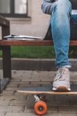 Fotografia vista parziale delluomo che si siede sul banco con skateboard e libri di testo liberi