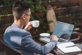 asian businessman with cup of coffee remote working in cafe