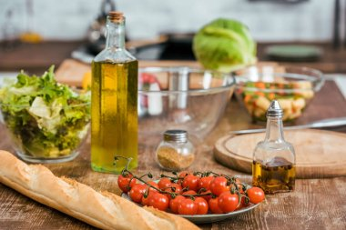 ripe fresh vegetables for salad, bottle of olive oil and baguette on tabletop in kitchen