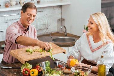 smiling couple preparing salad for dinner together in kitchen