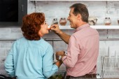 Fotografie back view of smiling man feeding beautiful mature woman while standing together in kitchen