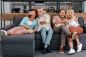 Középkorú/idős párok, ül a kanapén, és nézi a tv együtt félek