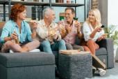 Fotografie Happy zralé muže a ženy jíst pizzu a pití piva při používání vzdáleného řadiče a sledování televize společně doma