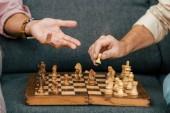 Fotografie Oříznout záběr mužů hrajících šachy společně na gauči
