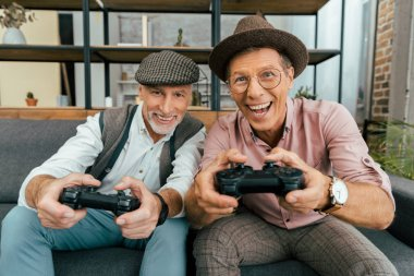 excited mature men playing with joysticks and smiling at camera