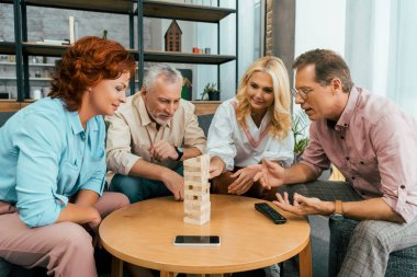 two mature couples spending time together and playing with wooden blocks at home