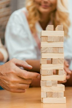 cropped shot of mature people playing with wooden blocks on table at home