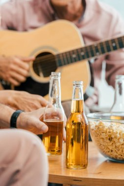 cropped shot of mature friends drinking beer and playing acoustic guitar