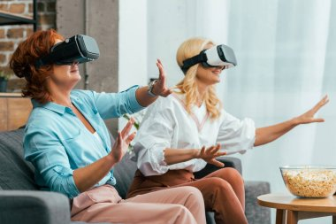 happy mature women sitting on couch and using virtual reality headsets