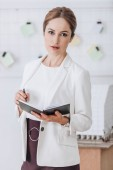 beautiful confident businesswoman in formal wear working with diary in modern office