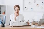Fotografie zamyšlená žena architekt při pohledu na house modelu v úřadu