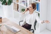 beszélő smartphone modern hivatalban-val laptop üzletasszony izgatott