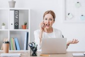 aggressive business woman yelling and talking on smartphone in office with laptop