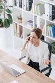 krásné zdůraznil obchodní žena mluví o smartphone v kanceláři s notebookem