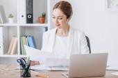 krásné výkonné podnikatelka pracující s dokumenty a notebook na pracovišti v moderní kanceláři
