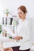 atraktivní obchodní žena dělá papíry sedí na stole v kanceláři