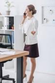 Happy profesionální podnikatelka na smartphone v moderní kanceláři