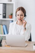 Krásné ženské operátor práce s headsetem a notebooku v moderní kanceláři