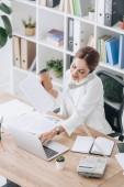 mosolyogva üzleti nő gazdaság dokumentumok és kávé menni, miközben beszél a telefonon, és dolgozik a laptop az office