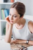atraktivní podnikatelka promyšlené sedí na pracovišti v moderní kanceláři