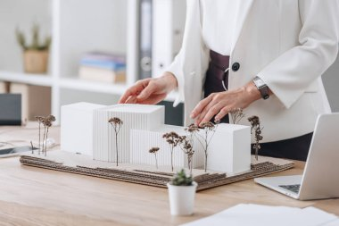 cropped view of female architect with house model at workspace