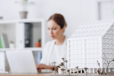 selective focus of house model and architect working with laptop in office